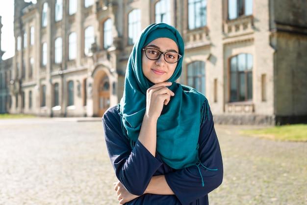 ヒジャーブを着ているイスラム教徒のイスラムの若いビジネス女性の笑みを浮かべてください。メガネで幸せなアラブの女子生徒。 Premium写真