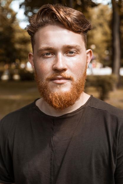 ひげとスタイリッシュな散髪と赤毛の若い男の肖像 Premium写真