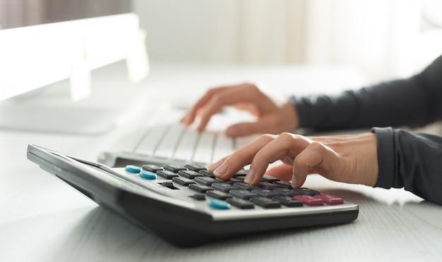 金融アナリストの手は電卓とコンピューターで働いています。職場での女性会計士。 Premium写真