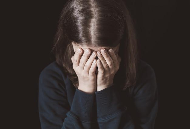 黒い背景に彼女の手で彼女の顔を覆っている女性の叫び Premium写真
