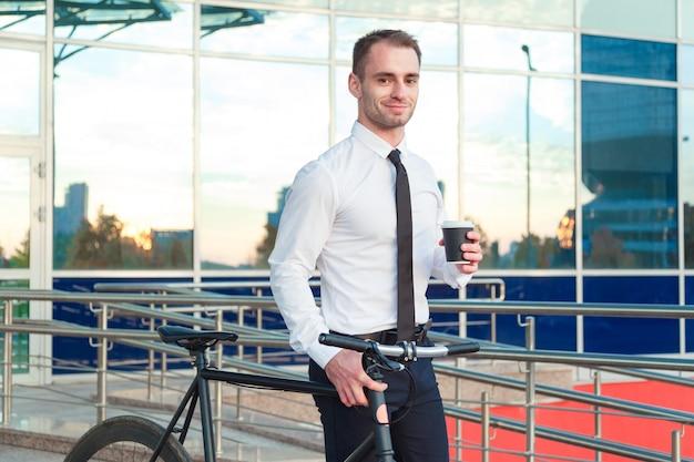Человек в костюме, держа чашку кофе, шел по улице с его велосипед. Premium Фотографии