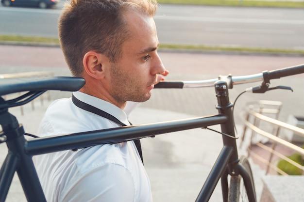 白いシャツと黒いネクタイでハンサムな青年実業家は彼の自転車を運ぶ Premium写真