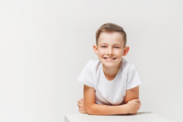 白で隔離、白で若い笑顔かわいいティーンエイジャーの肖像画を間近します。 Premium写真