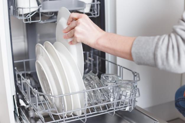 家事:食器洗い機に皿を置く若い女性 Premium写真