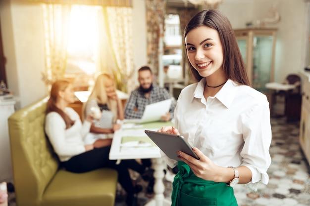 カフェに立っている笑顔若いウェイトレスの肖像画 Premium写真