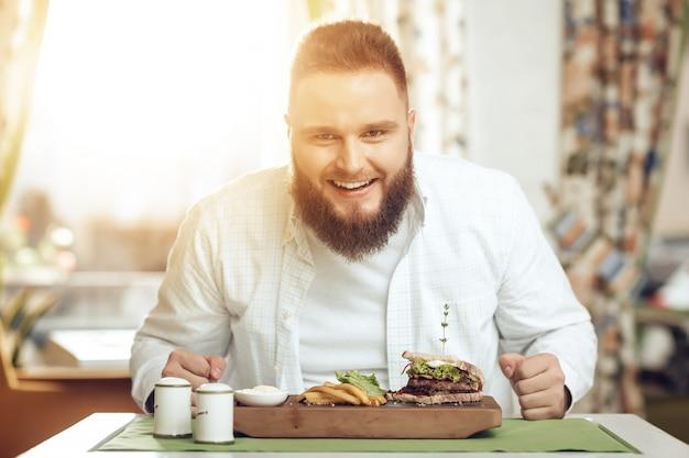 カフェで食べると食べ物を楽しむ人の肖像画 Premium写真