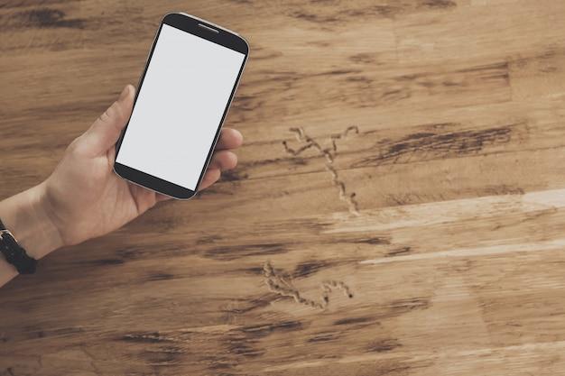 タブレットモバイルの背景を保持している手の上から見る Premium写真