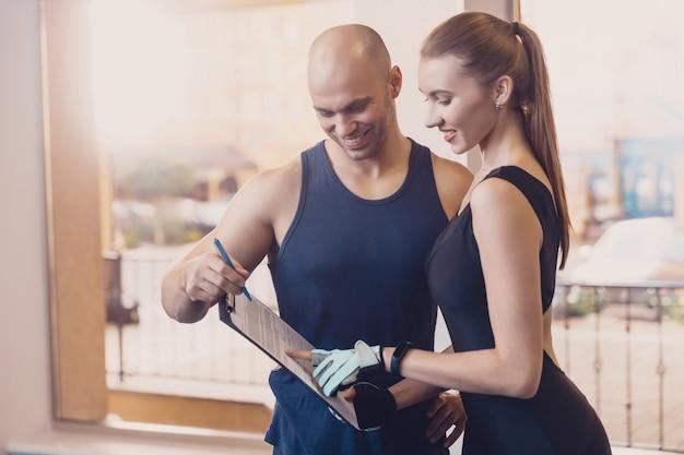トレーナーは、女の子をトレーニングするフィットネスプログラムを書きます Premium写真
