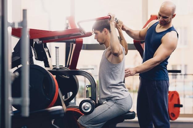 トレーナーは男の身体運動を制御します Premium写真