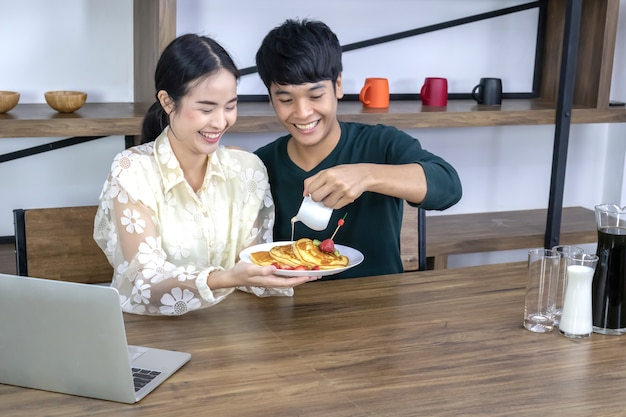 十代の若者たちは、イチゴのパイに蜂蜜を注いでいます。 Premium写真