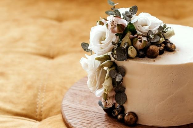 Белый свадебный торт украшен цветами эустомы и эвкалипта. место для текста. Premium Фотографии