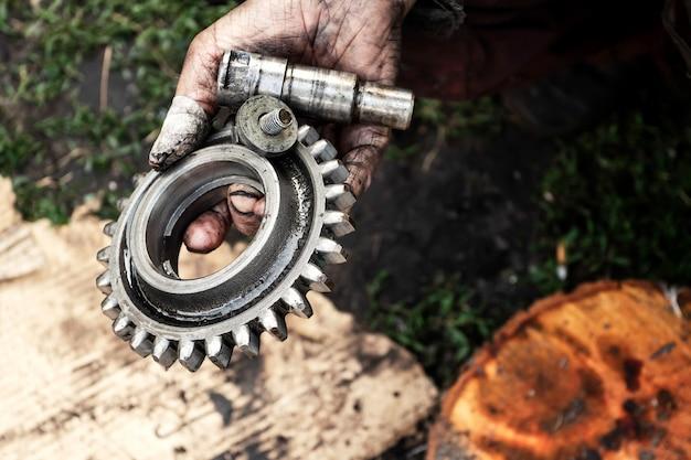 男はトラクター、農業機械のエンジンを修理します。汚れた手のベアリング。 Premium写真