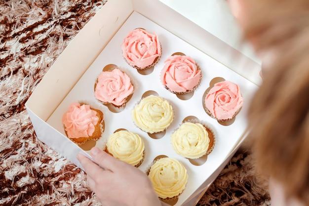 茶色の背景に紙箱にピンクと黄色のクリームのカップケーキ。 Premium写真