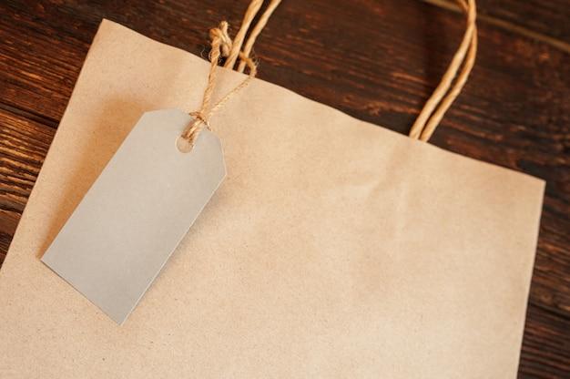 ヴィンテージの木製テーブル上のタグとモックアップクラフト紙ショッピングバッグ Premium写真