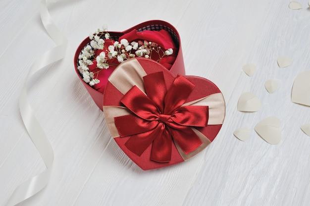 素朴なスタイルの聖バレンタインの日のハート型の赤いボックス Premium写真