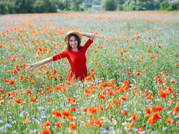 ケシの花のフィールドに麦わら帽子で素敵な若い女性 Premium写真