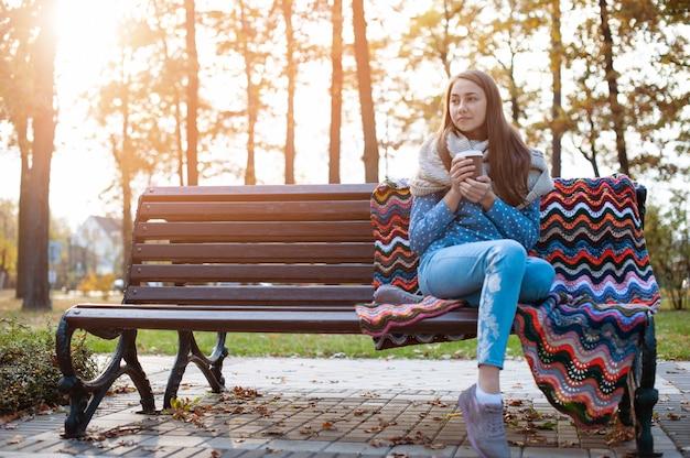 秋の公園のベンチに座って、コーヒーを飲みながら若くて魅力的な女の子 Premium写真