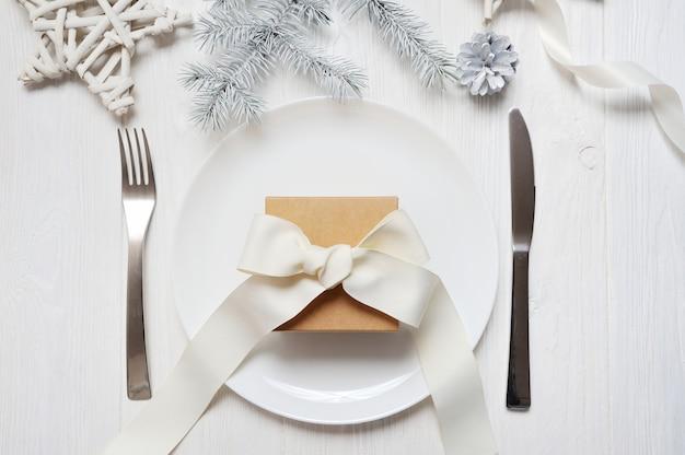 白い木製のテーブルにビンテージギフトとクリスマステーブルの設定 Premium写真