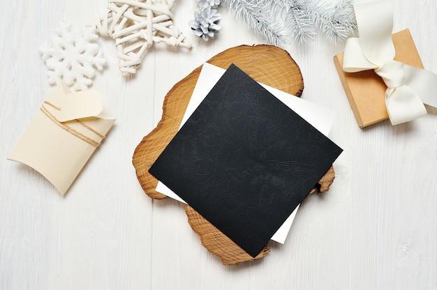封筒と白い木とギフトのモックアップクリスマス黒グリーティングカードの手紙 Premium写真