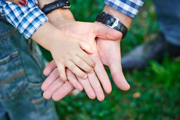 Мама и папа держат ребенка за руку Premium Фотографии