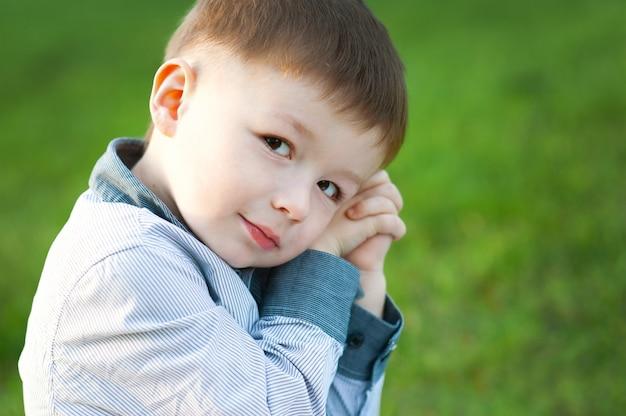 かわいい男の子は緑の芝生に座っています。彼は待っています。子供たちの幸せ Premium写真