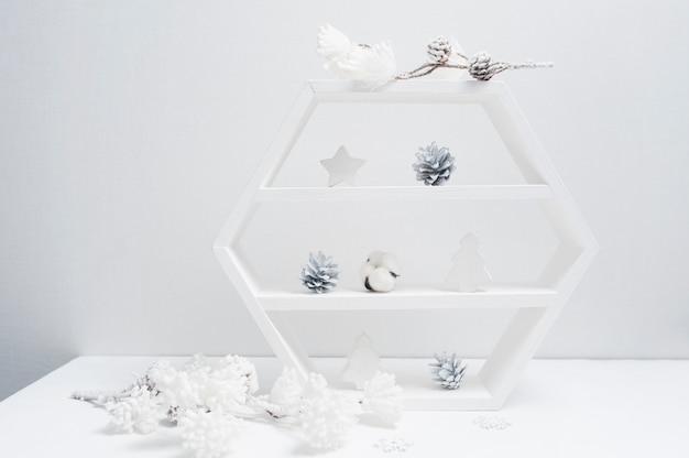 Декоративный белый книжный шкаф с декором рождество. шишки, хлопковые цветы Premium Фотографии