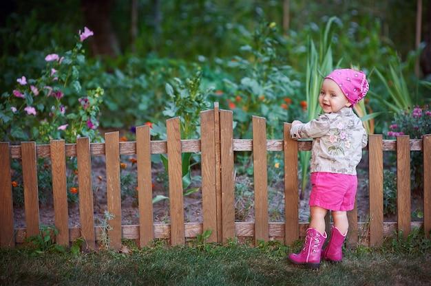 フェンスの近くのピンクの靴の少女 Premium写真