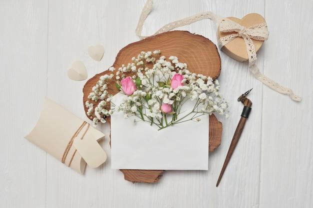 書道の羽の花と手紙、ハートバレンタインギフトボックス、グリーティングカードと封筒 Premium写真