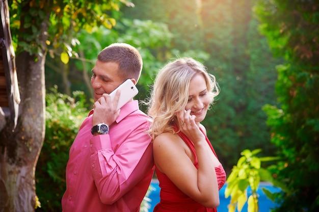 Мужчина и женщина в красном платье разговаривают по телефону друг с другом Premium Фотографии