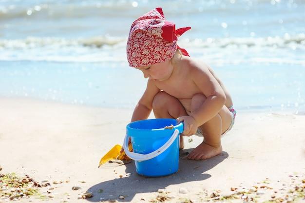 小さな女の子は海で青いバケツで遊んでいます。 Premium写真