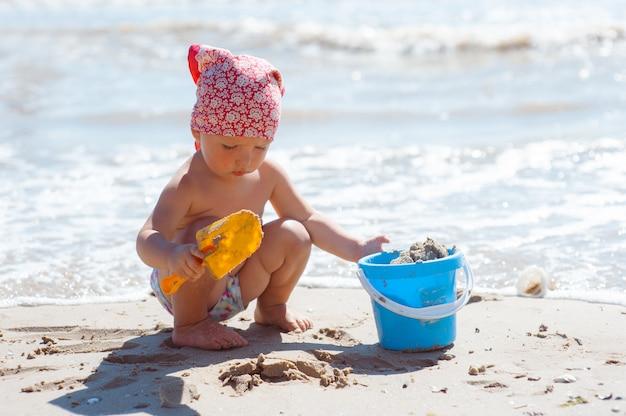少女がビーチで砂の城を構築 Premium写真
