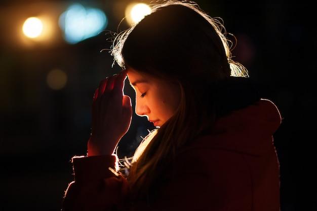 祈っている若い女性のクローズアップの肖像画 Premium写真