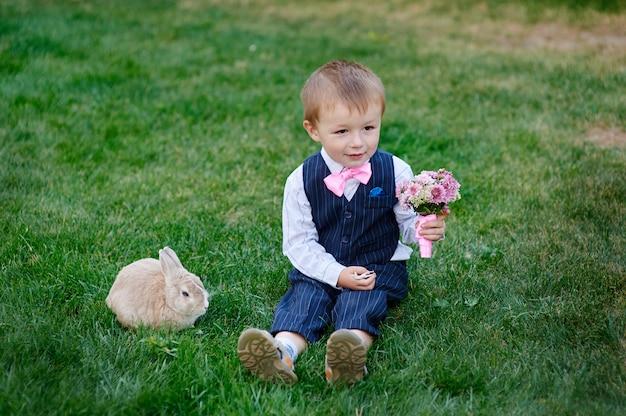 花束と草の上に座っているウサギの小さな男の子 Premium写真