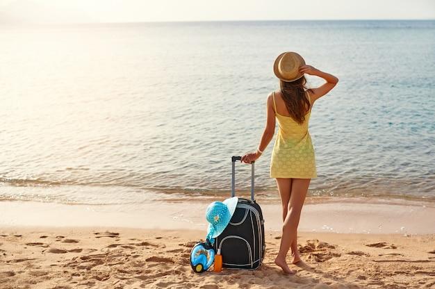 Красивая молодая женщина в шляпе стоит с чемоданом на прекрасном море Premium Фотографии