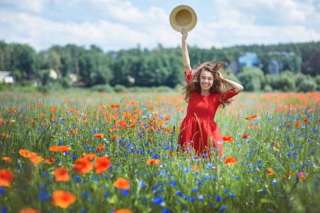 ケシの花のフィールドに麦わら帽子の素敵な若いロマンチックな女性 Premium写真