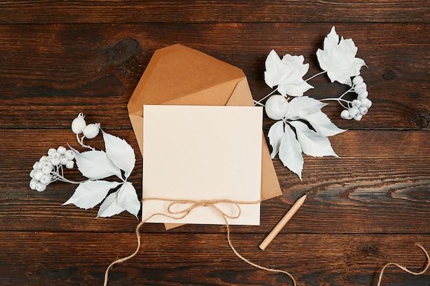 白の封筒と空白のクラフトグリーティングカードの上から見る、 Premium写真