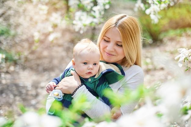 開花春の庭で彼女の若い母親と小さな男の子 Premium写真