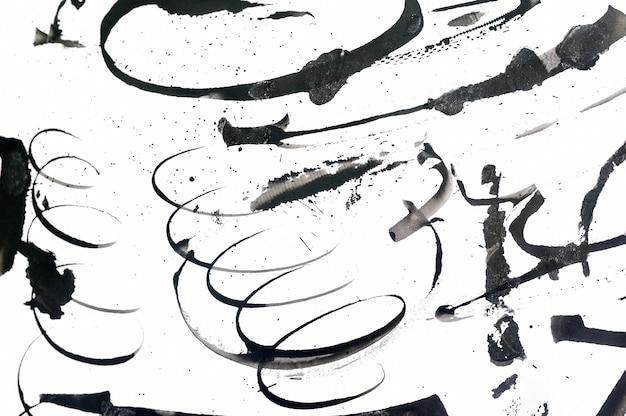 黒の抽象的なブラシストロークと紙の上の塗料の飛散。グランジアート書道の背景 Premium写真