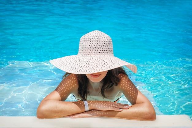 プールで休んでいる白い帽子の若い女性 Premium写真