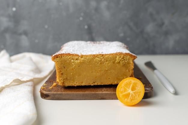 木製のまな板にキンカンとオレンジのケーキ Premium写真