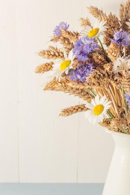 Спелая пшеница в белой вазе на деревянном фоне Premium Фотографии