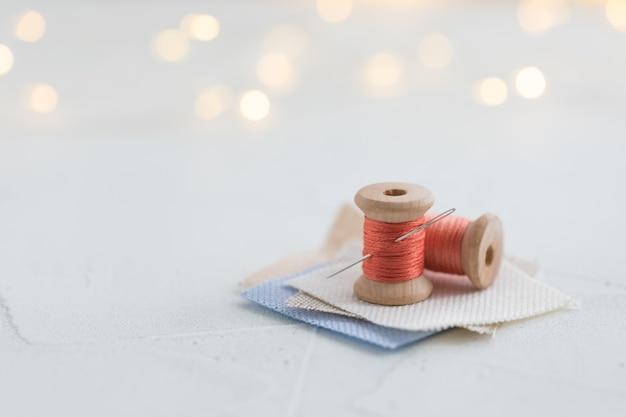 白い背景の上のリネンパックに針でステッチするためのサンゴ色スレッド木製ボビン Premium写真