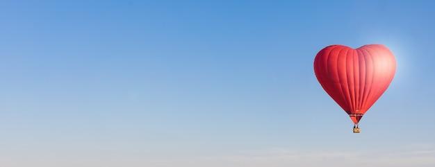 赤いハート形の空気風船、空のバナーで分離 Premium写真