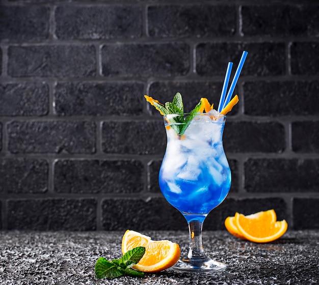 氷とオレンジの青いカクテルドリンク Premium写真
