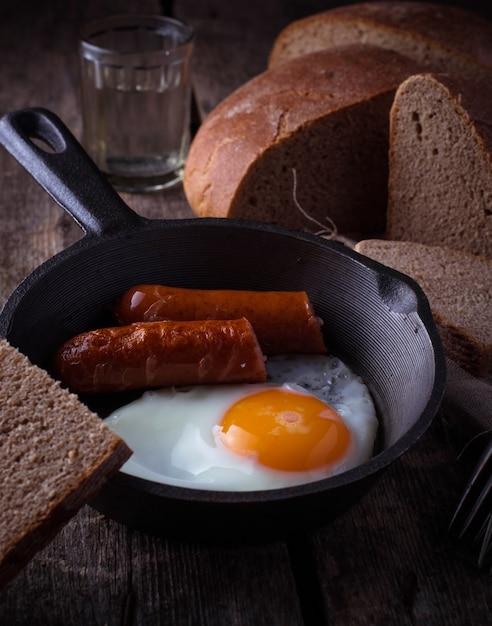 鍋にソーセージと目玉焼き。セレクティブフォーカス Premium写真