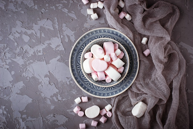 Белые и розовые зефиры на сером фоне бетона. выборочный фокус Premium Фотографии