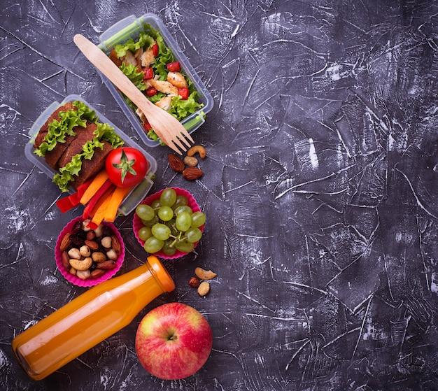 学校給食。サラダ、サンドイッチ、フルーツ、ナッツ Premium写真