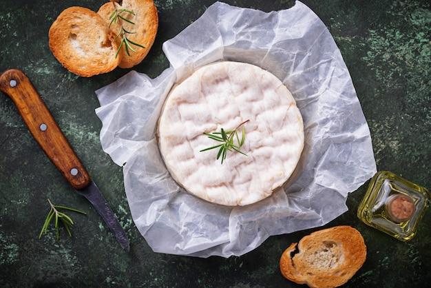 Сыр камамбер с розмарином на зеленом фоне Premium Фотографии