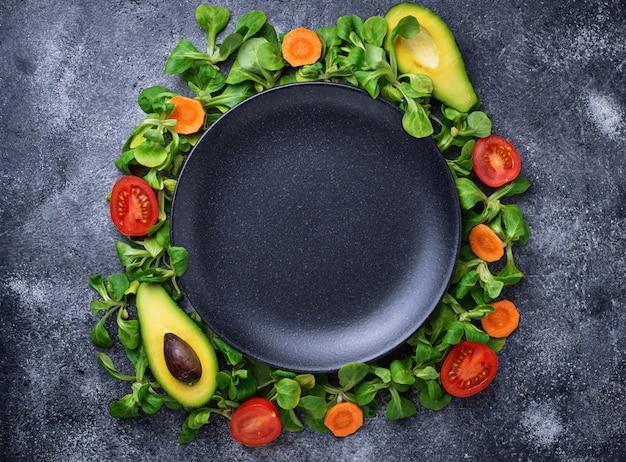 Рамка из овощей вокруг тарелки. Premium Фотографии