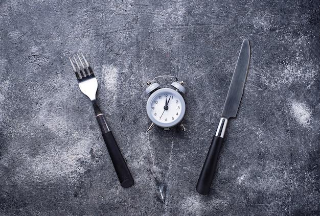 ナイフとフォークでグレーの目覚まし時計 Premium写真